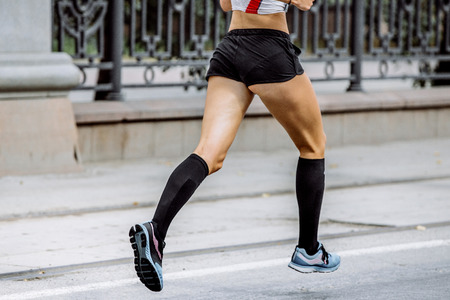 61632018 - side view of young woman legs in compression socks athlete running a marathon